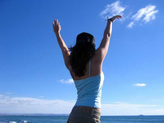 woman-against-blue-sky-arms-high-simon-younes